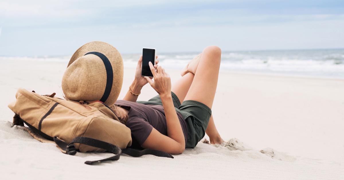 woman scrolling phone on beach