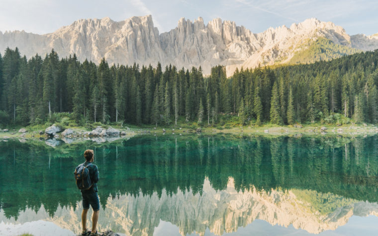 Man standing and looking at Lago di Carezza in Dolomites