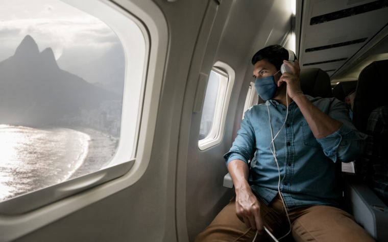 Man traveling by plane wearing a facemask and looking at Rio through the window